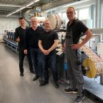 From left to right: Michael Koch from Heidelberg Deutschland, with Eugen Kölling (owner), Andreas Hansen (head of production) and Stefan Bollens (operator) from HP-ETIKETT in front of one of the two Labelmaster, both installed in 2021 (Picture Source : Gallus Ferd. Rüesch AG)
